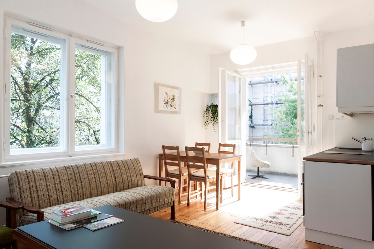 The living room has an open kitchen and is filled with light.