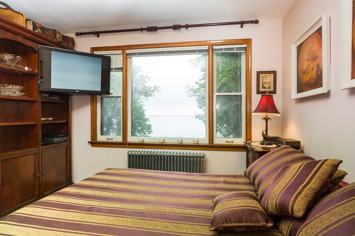 Master bedroom with king size bed, overlooking Lake Ontario.