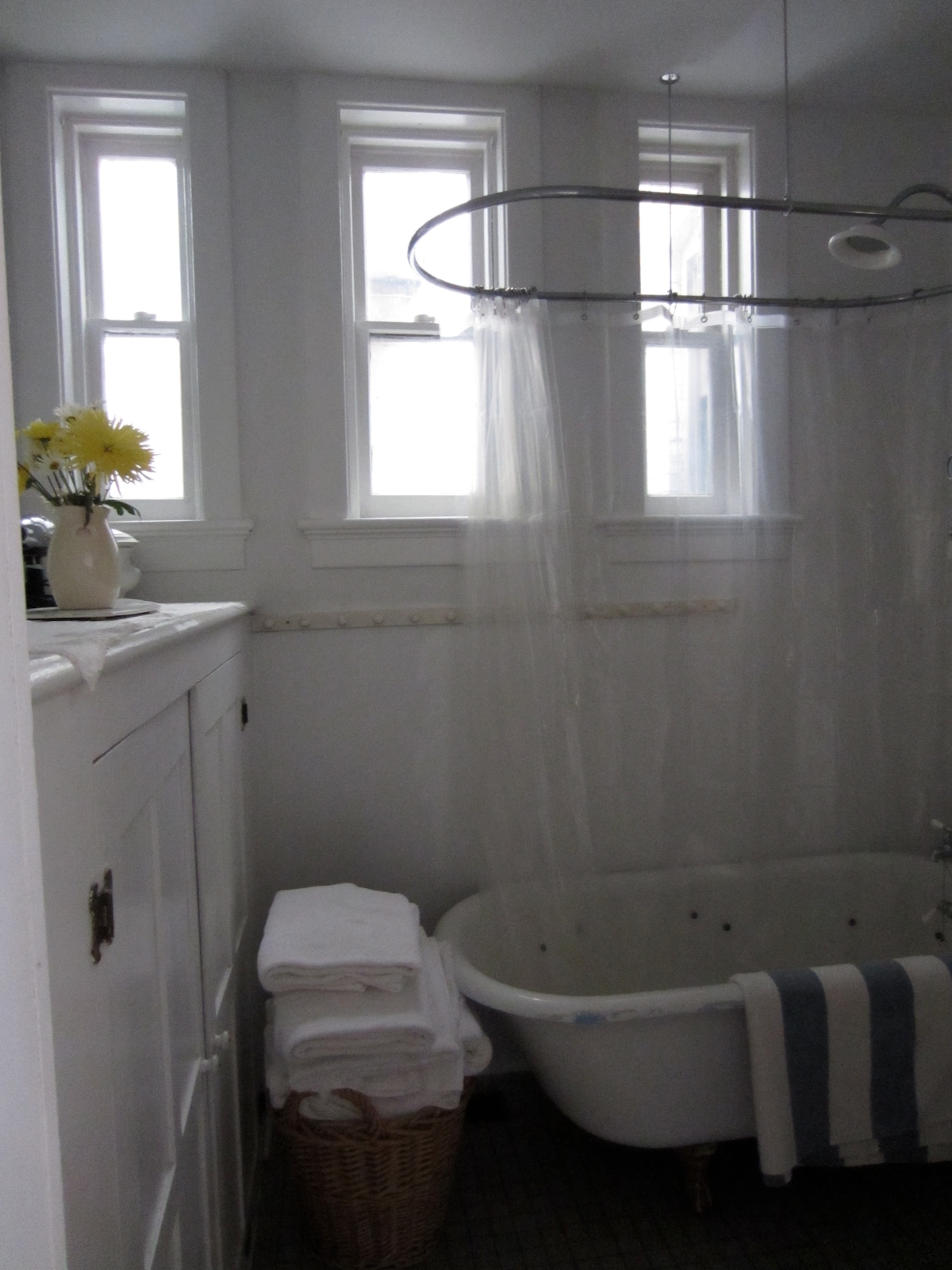 The traditional bathroom with old fashioned cupboards, clawfoot tub-shower are located just downstairs.