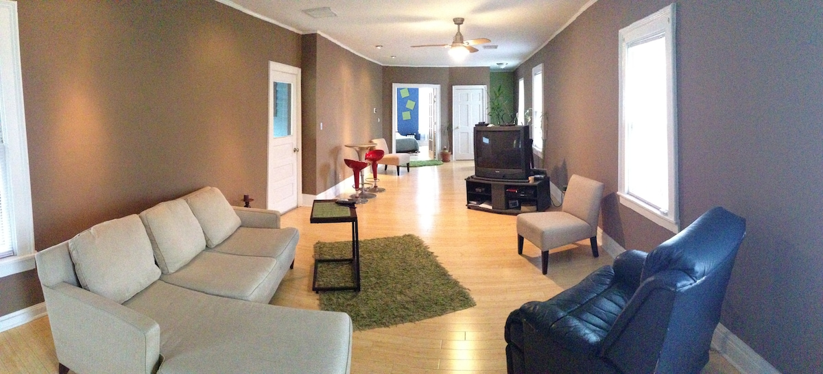This is the main living area. It's a wide open floorplan with hardwood floors, L shaped couch, pub table and TV.