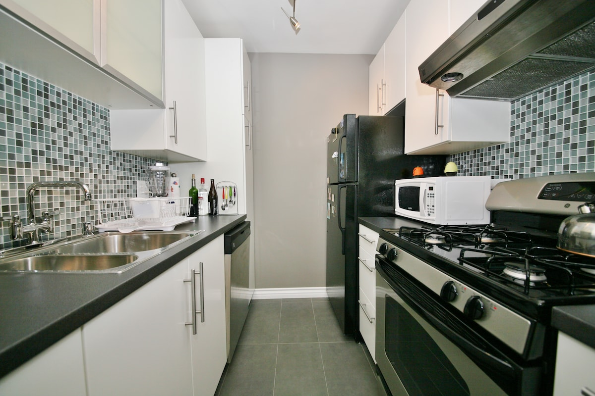 New galley Kitchen with glass tiles...modern styling.
