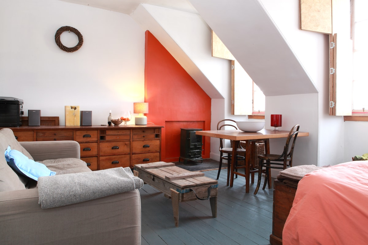 Front room, with stove and full length window shutters for a cosy feel in the winter.