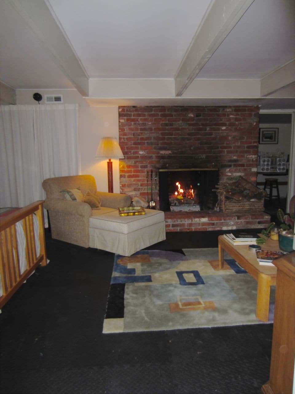 This is the view from the patio looking in to the fireplace and comfortable chair and ottoman