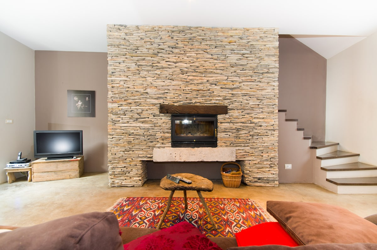 Main lounge room setting with traditional stone wall fireplace and cable tv.