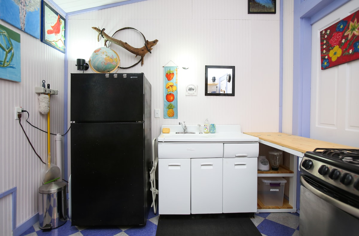 """Vintage porcelain sink and drainboard-- the name on its cabinet is """"Beauty Queen."""""""
