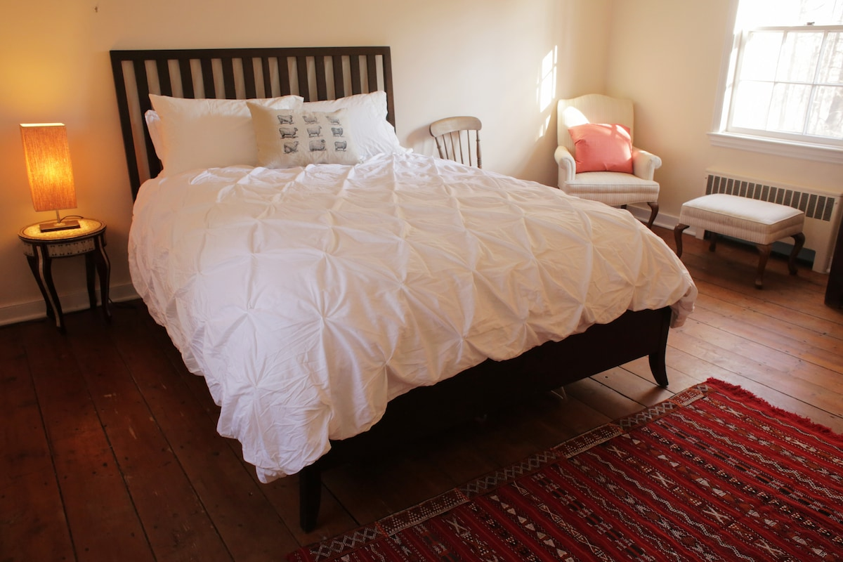 This quiet room at the back of the second floor has a queen-size bed, dresser, large closet, and a wingback chair.