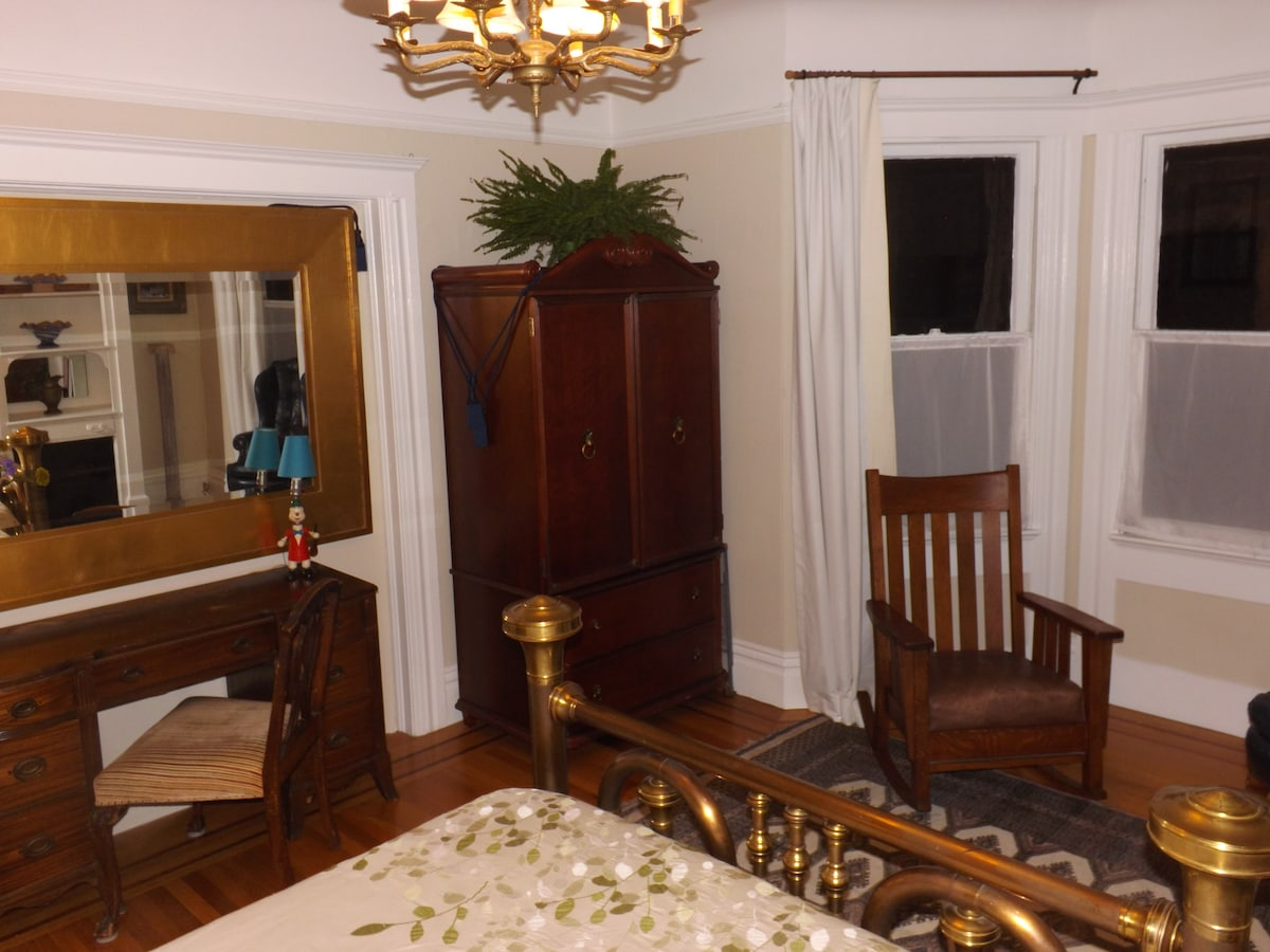 Room has large armoire and writing desk