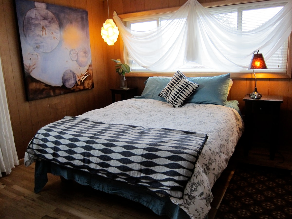 A comfortable queen sized bed alongside an original painting by a neighbor!