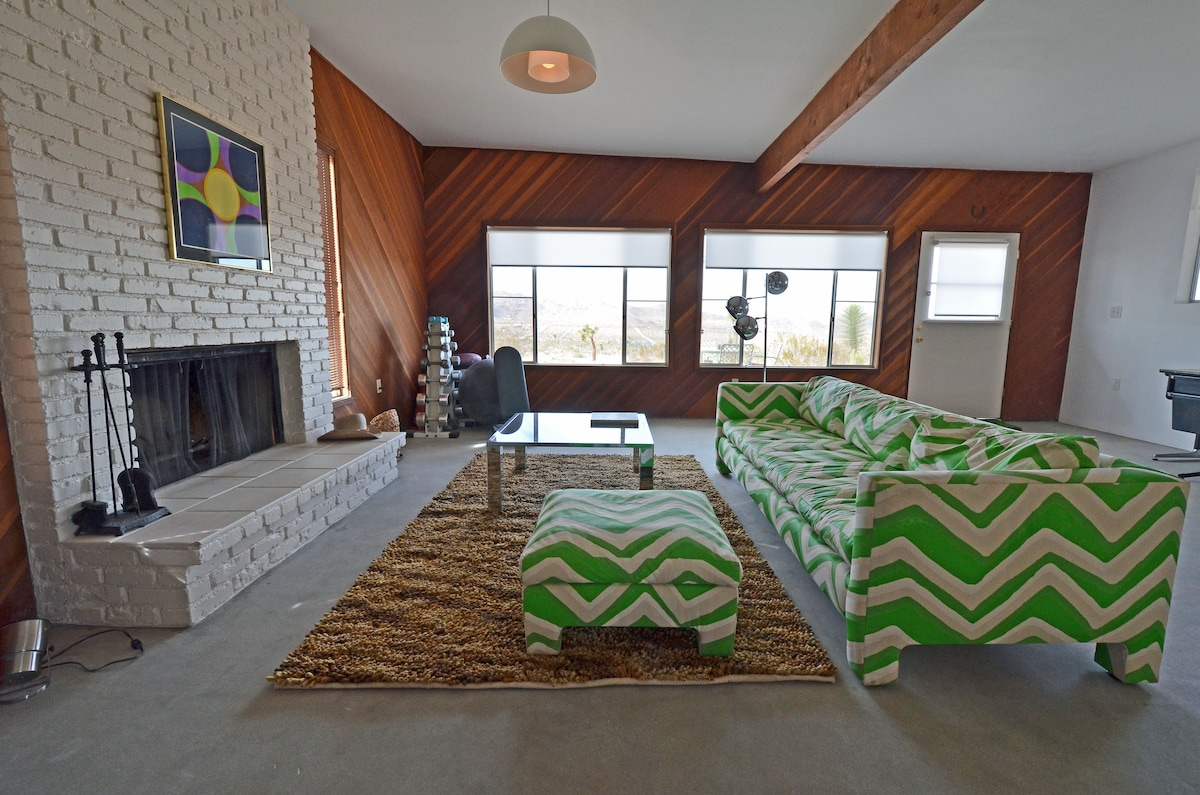 Living room area with wood-burning fireplace & views to the north.