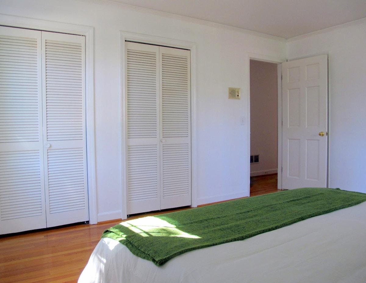 Another angle of the room and showing the door leading to the hall. The bathroom door is hidden behind the open bedroom door.