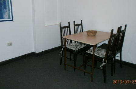 Dining table and chairs on one end of main room, next to kitchen.