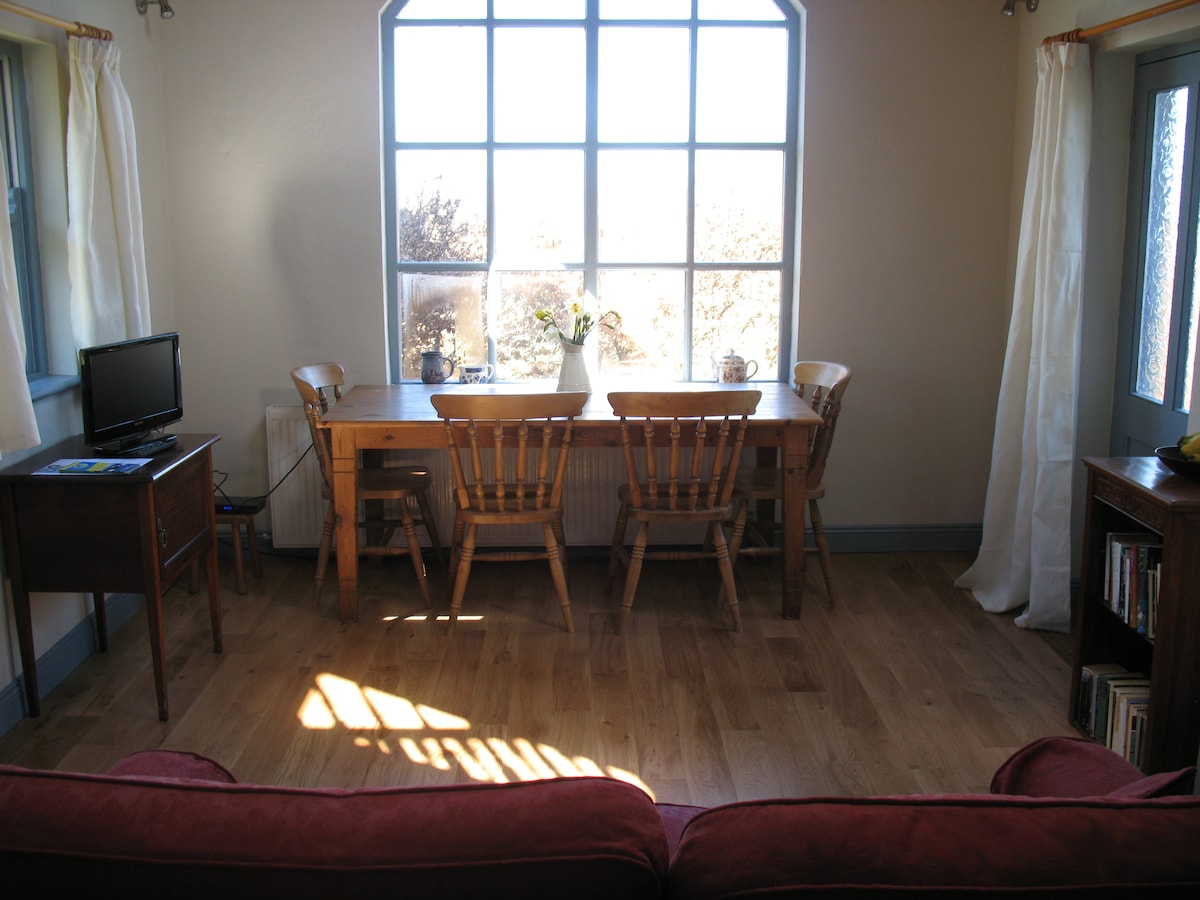 The living room of the cottage with picture window to the outside world. The strange apparition on the floor is called shadow, apparently it is caused by the sun. An extremely rare occurrence in Ireland, it cannot be guaranteed when you visit!