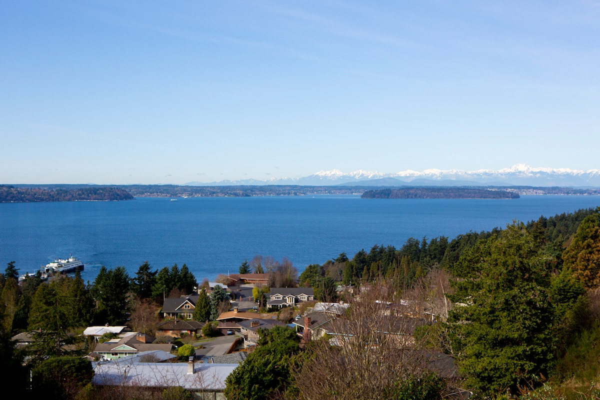 This is the gorgeous view from the back deck, there are no wires or houses blocking this stunning view! Puget Sound framed by the Vashon Ferry to the left and Blake Island State Park and the Olympic Mountains to the right.