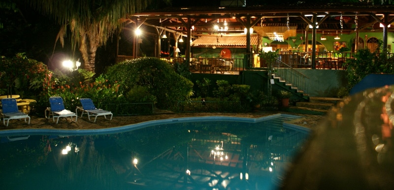 Pool area at night with villa in the background