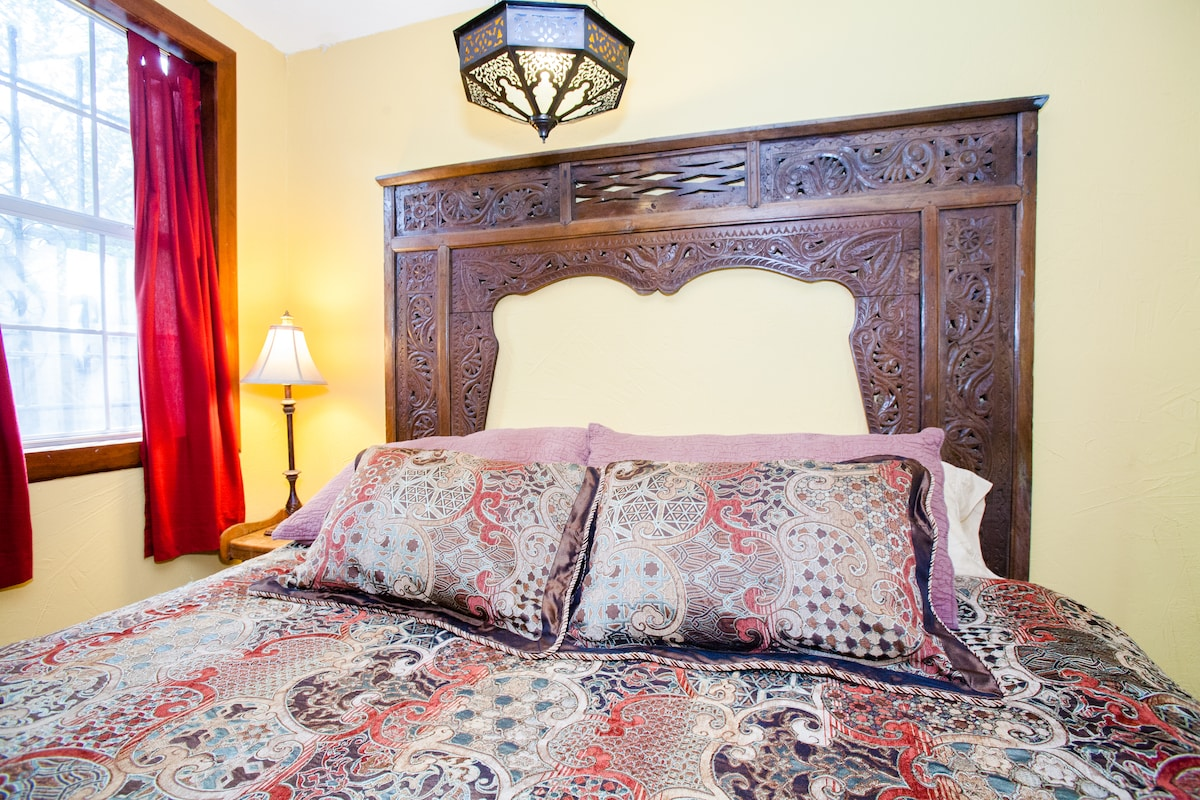 Hand-carved wooden Indonesian ventana as headboard frames the king size bed, with Syrian light fixture overhead