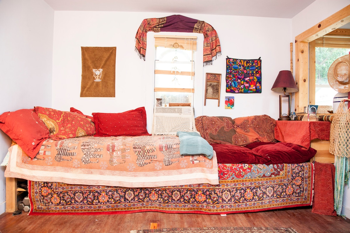 """The living room also has a twin size mattress on the """"couches"""" which also serve as storage."""