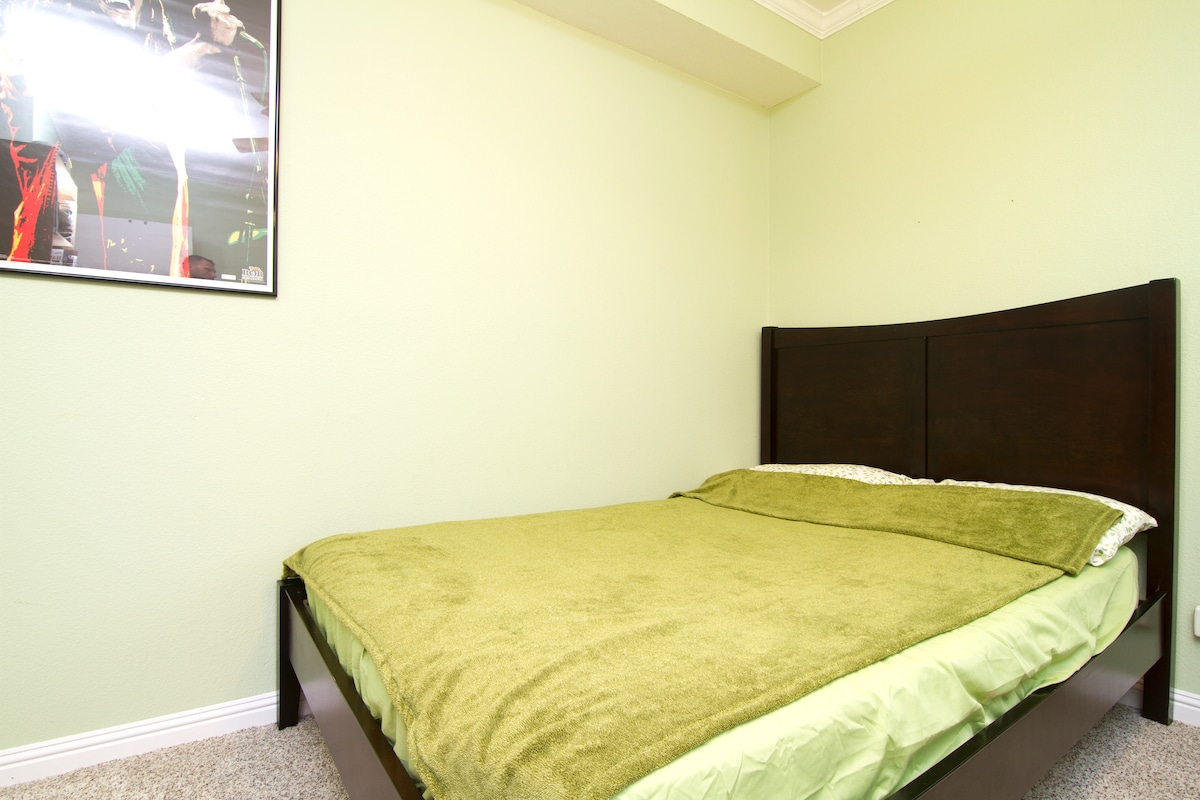 Guest room. Full bed with frame and headboard. Extra sheets and towels are stored in boxes underneath it.