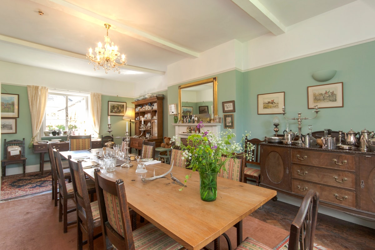 The dining room is bedecked with antique hunting, fishing and shooting pictures and prints