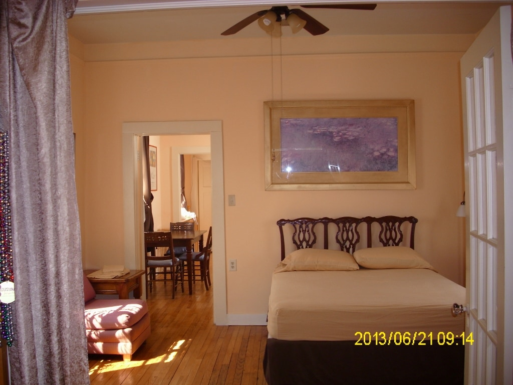 Master bedroom with queen size bed, speedy ceiling fan, air conditioner and TV