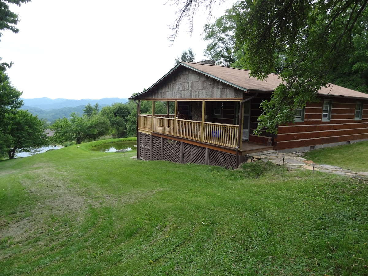 Mountain Song Cabin with hand hewn logs, wraparound porch, and layered views in every season