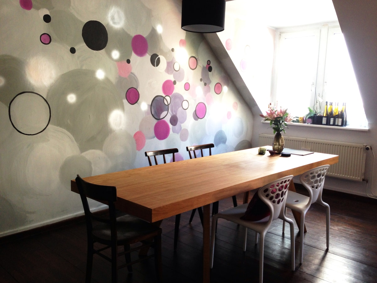Designer dining room table with 6 chairs and a funky wall