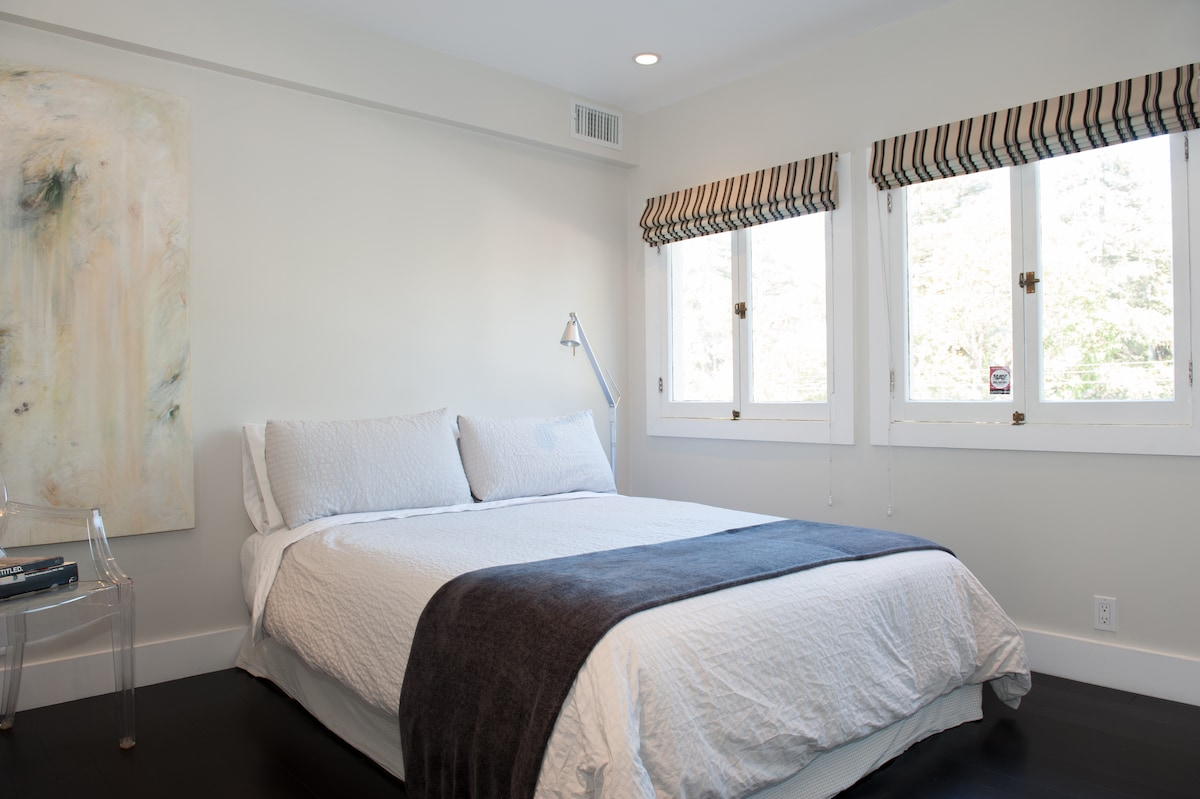 Airy contemporary studio apartment, view of queen size bed out east facing windows