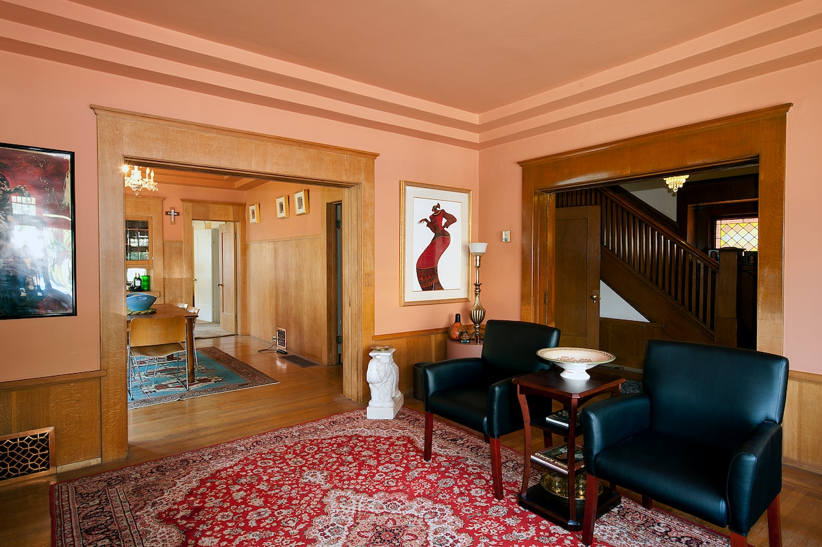 View of the living room, facing the dining room and stairs off to the right.
