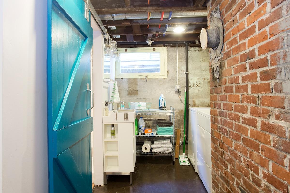 Original basement door reused as barn-style bathroom door, sink and laundry and cleaning stuff