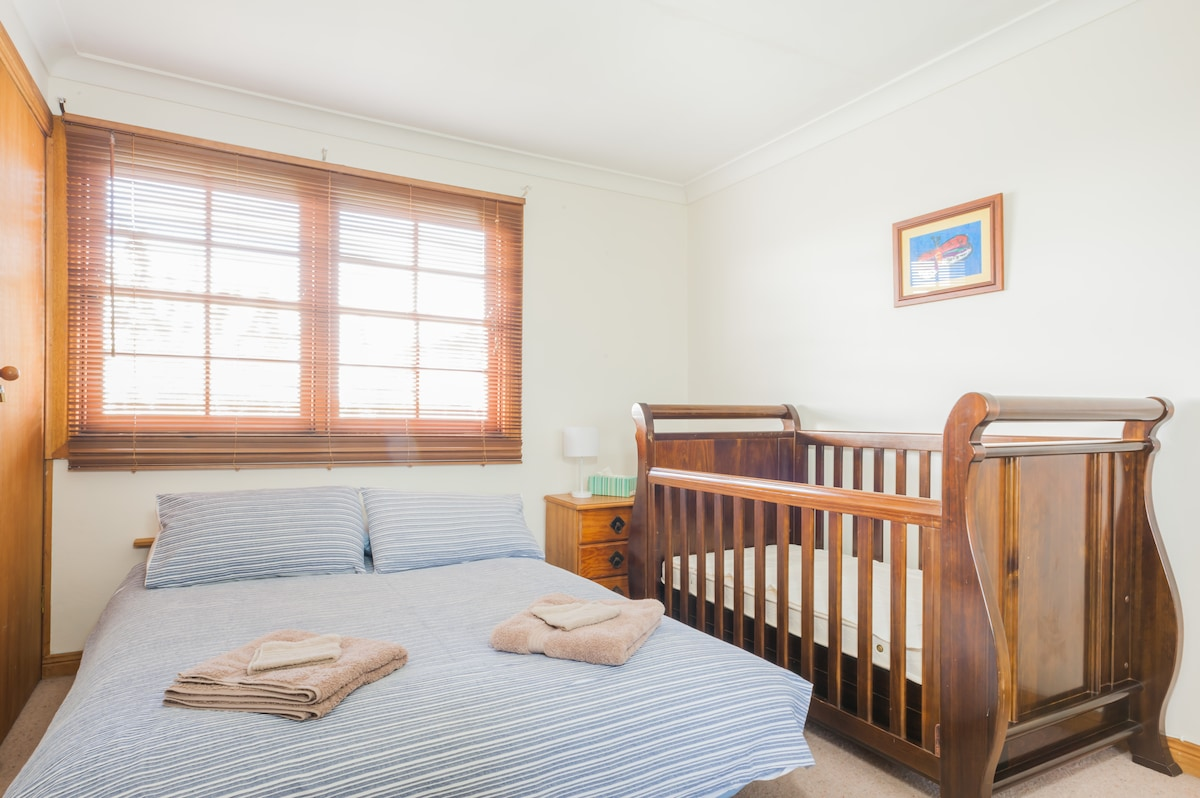 Bedroom 2; Double bed, potable cot and window view of the Pacific Ocean with new plush carpeting.