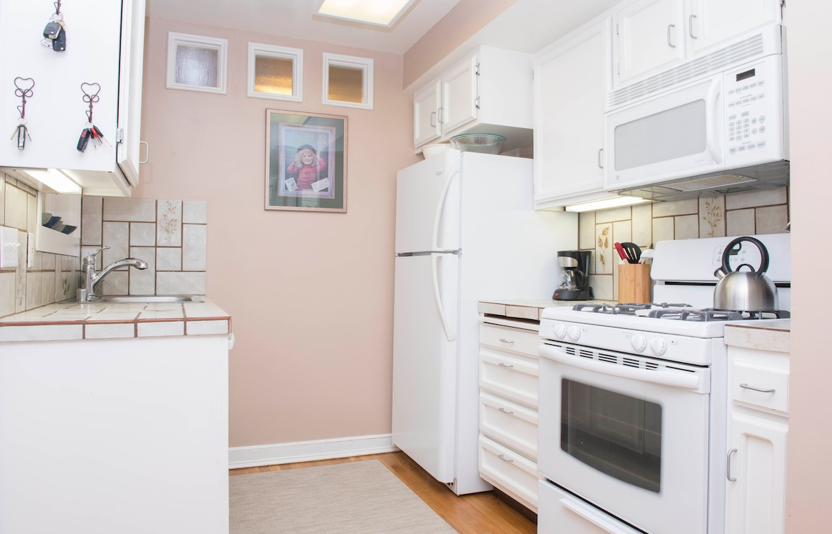 Kitchen with large dishwasher, gas range and fully stocked with coffee machine, plates, glasses, knives, flatware & cookware