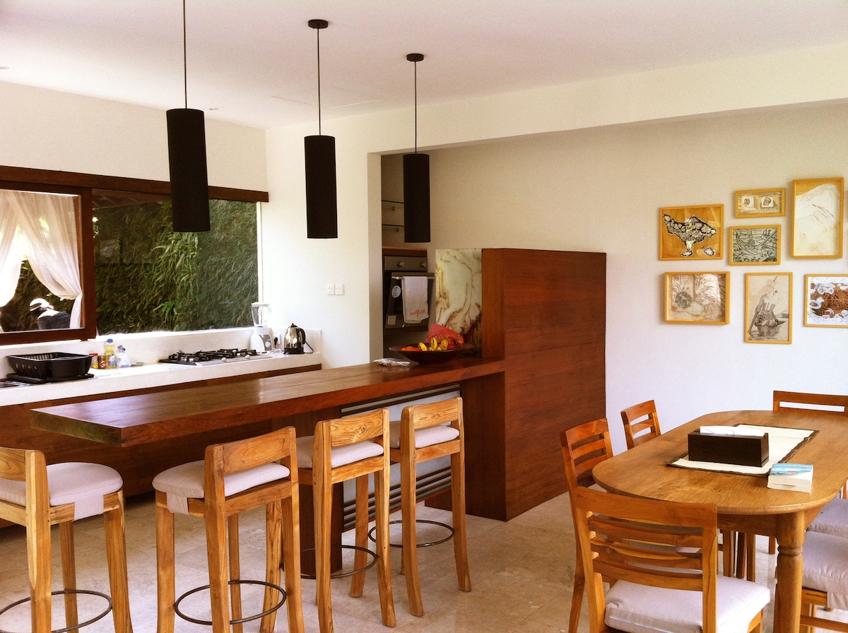 Full equipped kitchen with hand-made furniture and iron wood bar.