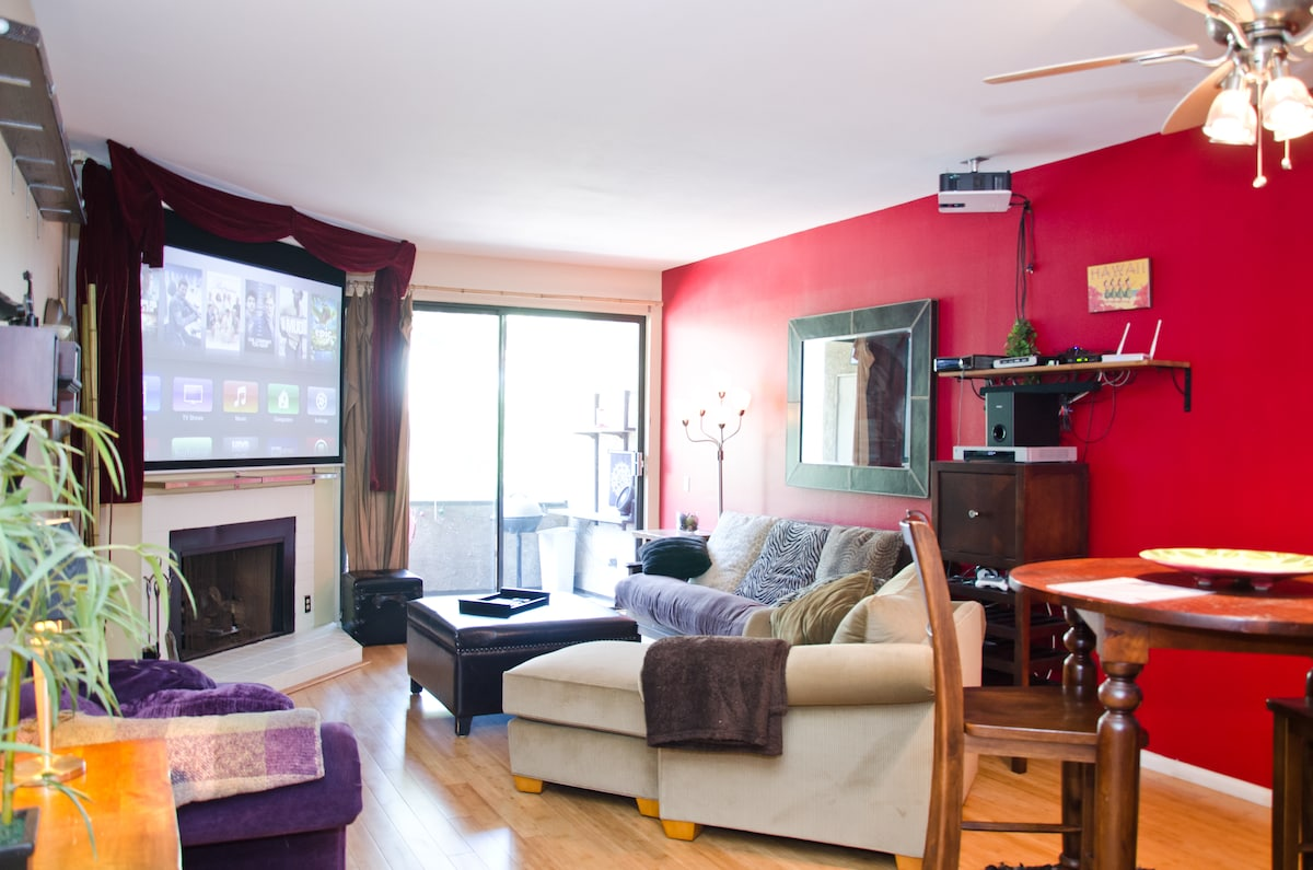 Living room features an Xbox, Apple TV, and Cable TV on a 92 inch HDTV. Hardwood floors, and full size futon.