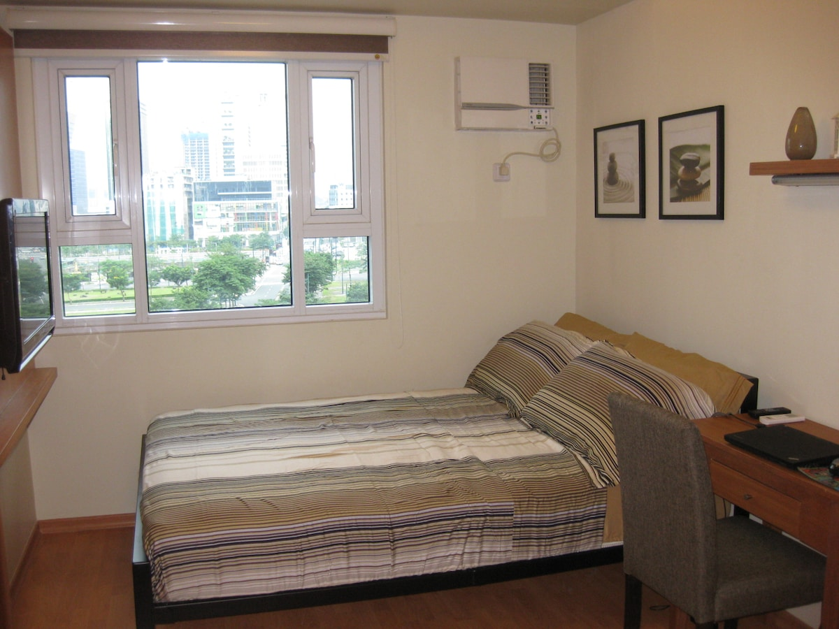 Bedroom with a view of Bonifacio High Street area.
