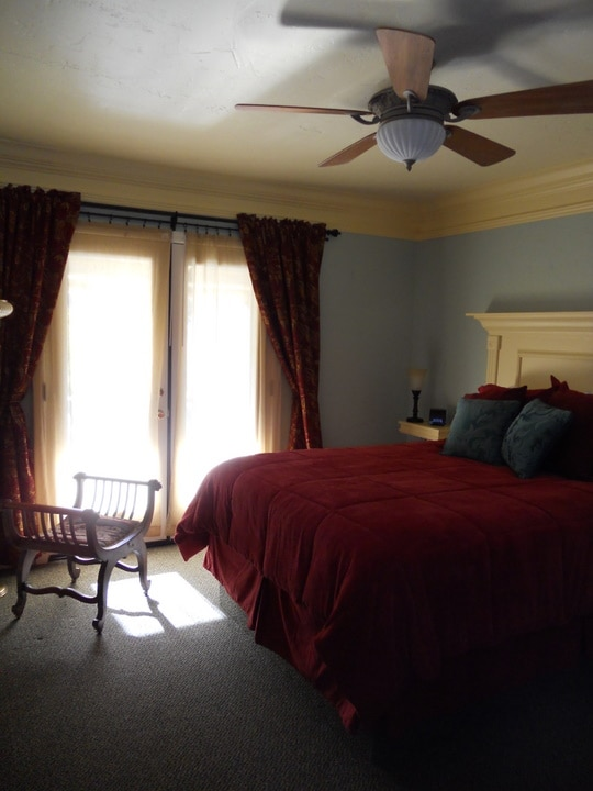 Spacious bedroom with a comfy queen bed. Handcrafted headboard and side tables. French doors lead out to you own private balcony overlooking Mariposatown.