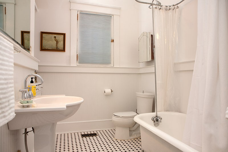 Downstairs bathroom with original, newly restored claw-foot tub, shower