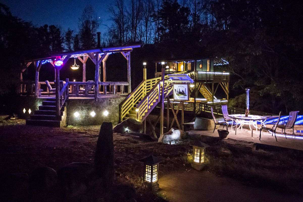 Tree house at night with stone gazebo at entrance and host house to the right.