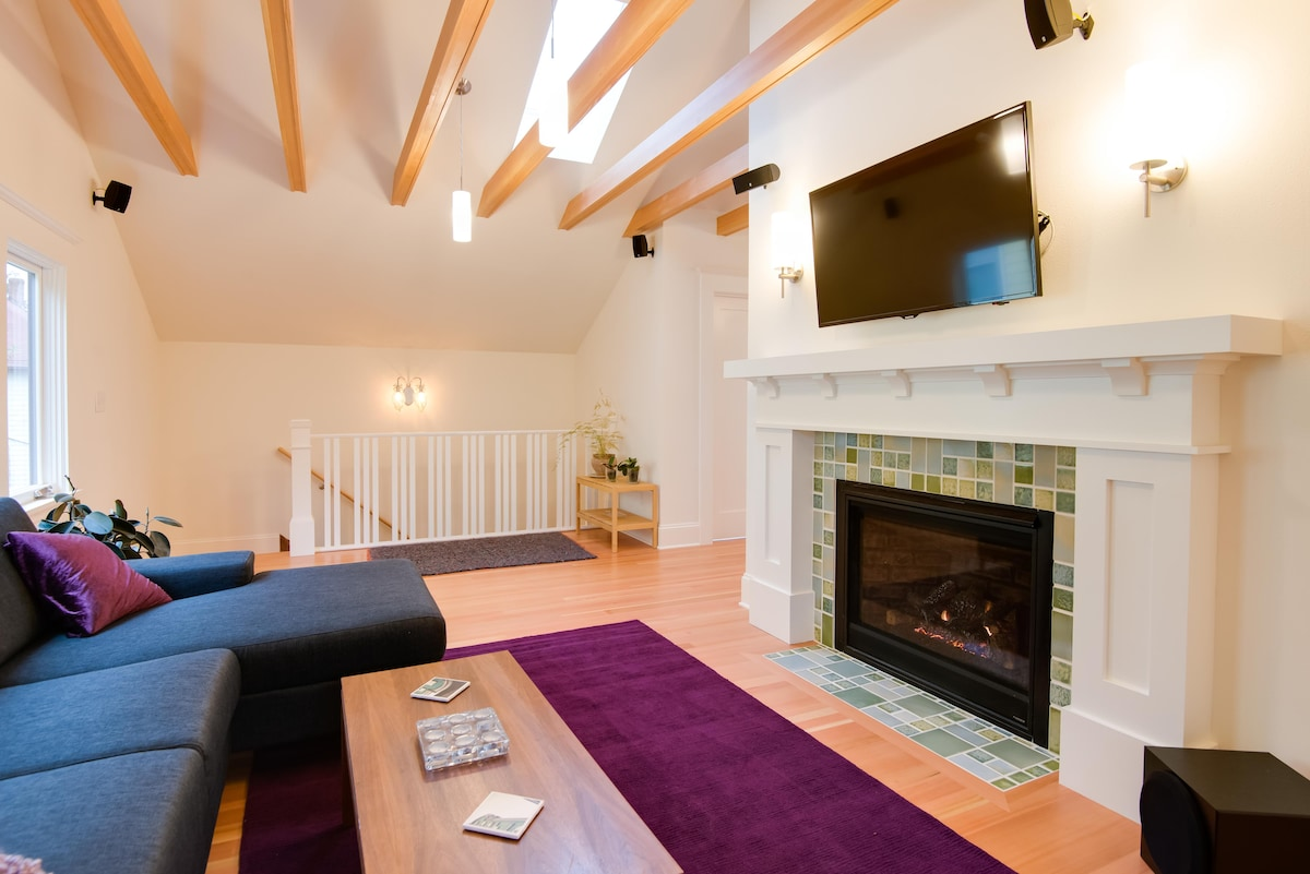 Light filled, private living room with fireplace, flat screen TV and surround sound system.