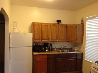 Fully equipped kitchen with refrigerator, toaster, coffee maker.