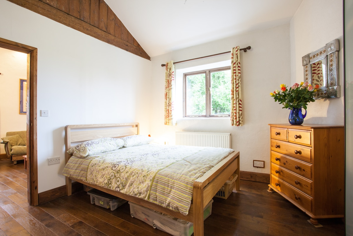 Bedroom with double bed, chest of drawers and fitted wardrobe for your use. Window overlooks a quiet garden.