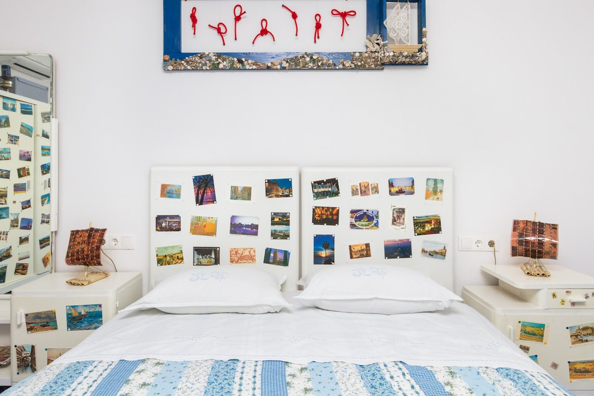 double bed with postcards and Kon-Tiki lamps