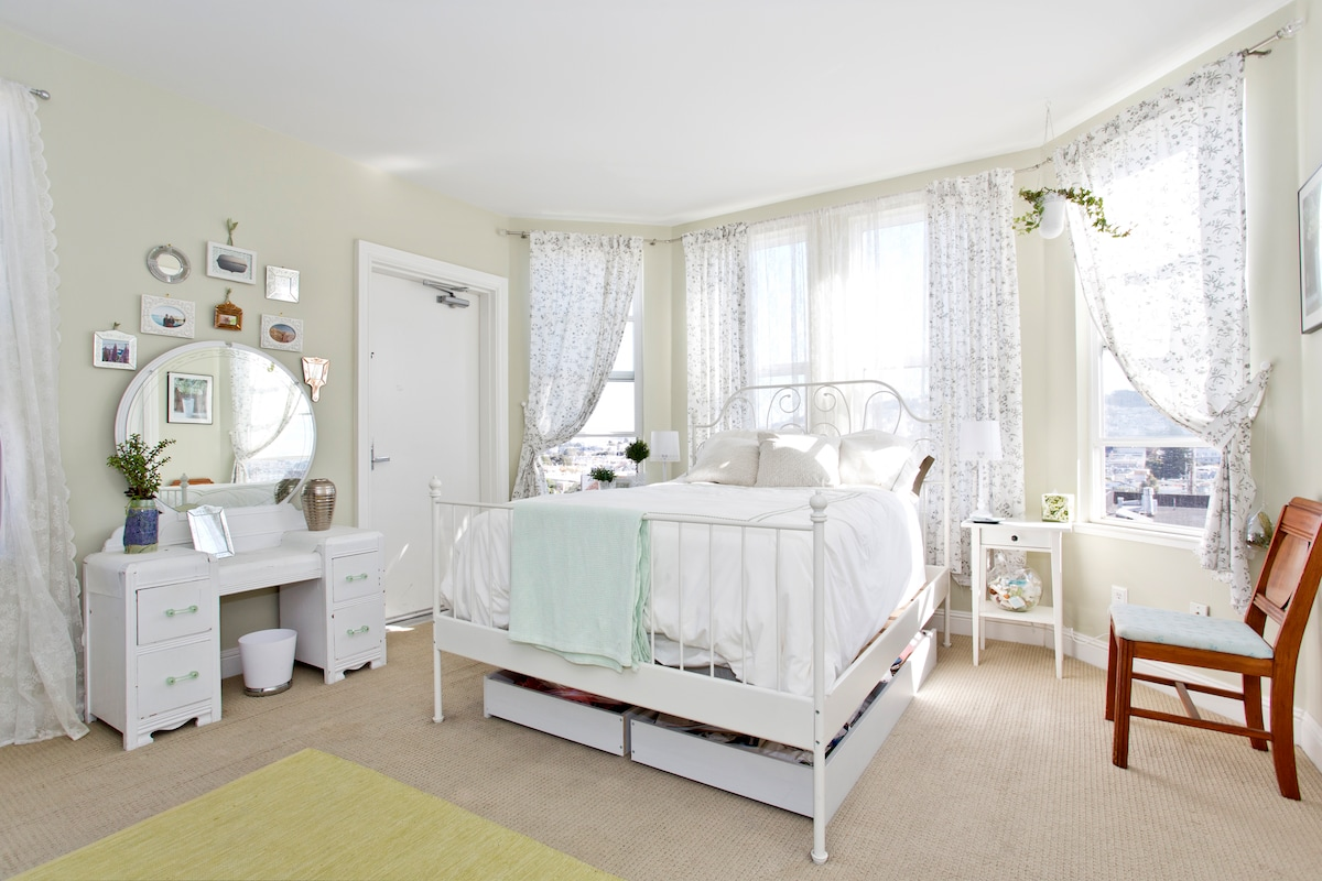 Airy, restful bedroom with full bed and reading lights on either side of the bed.