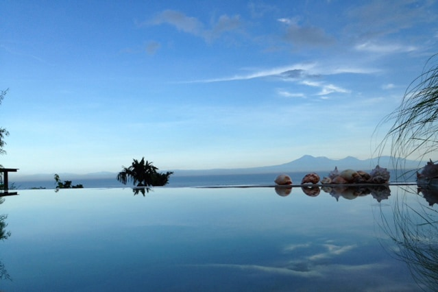 Swimming pool with Balinese mountains in the distance.