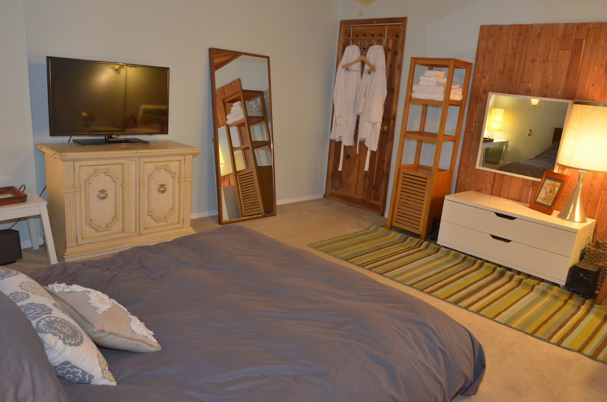 """The master bedroom has a 42"""" flat screen, soft terry cloth robes, & large mirrors that are perfect for yoga or tai chi!"""