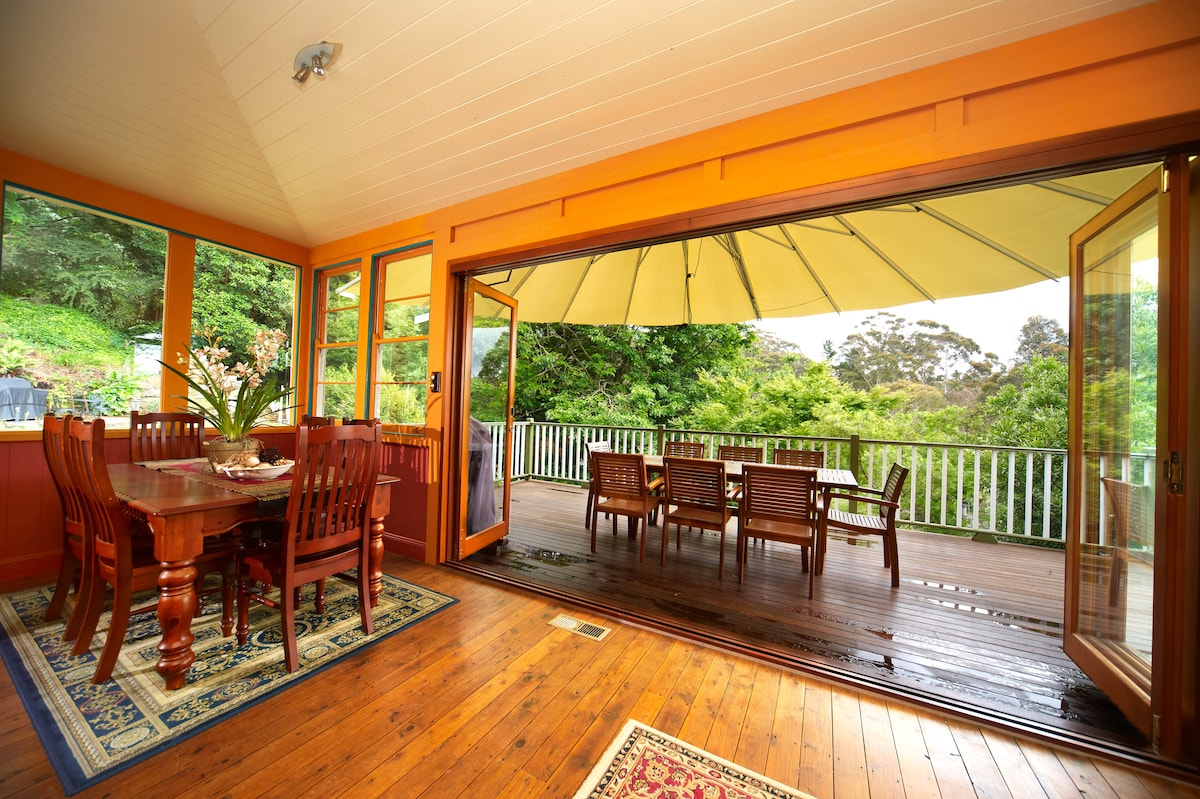 Concertina doors open out to the large deck overlooking the large lush grounds and stunning gardens and birdlife
