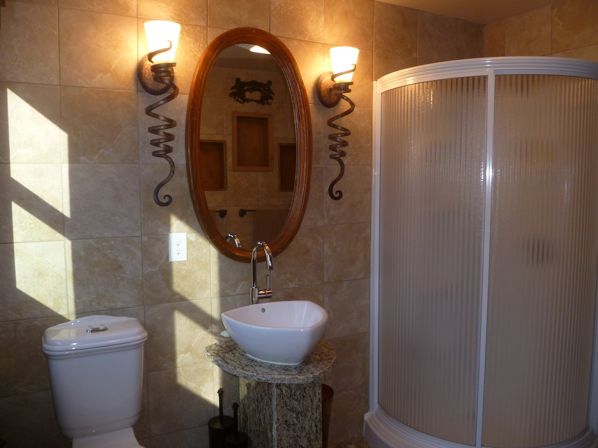 Tapestry Suite Bathroom with Quarter Round Shower and Custom Furnishings