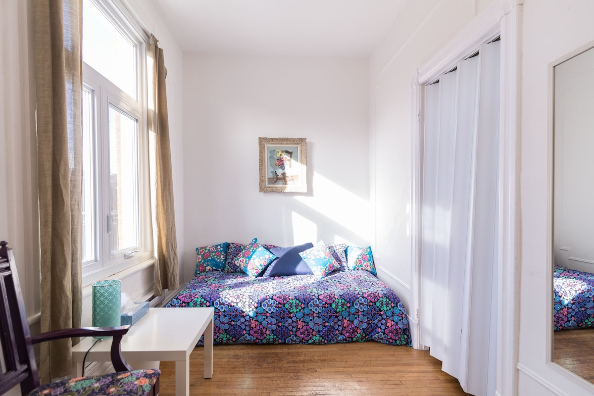 Small front room with single bed.  Look at that sunshine!