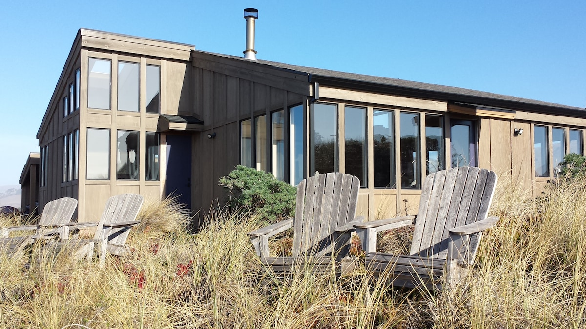 Oceanside of the house with Adirondack chairs just waiting for you to chill-lax.