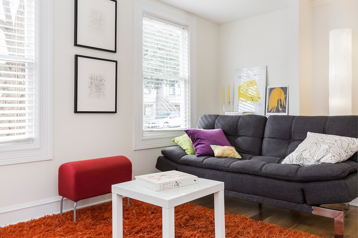The sitting room area, featuring the sleeper couch with Serta mattress and eclectic art.