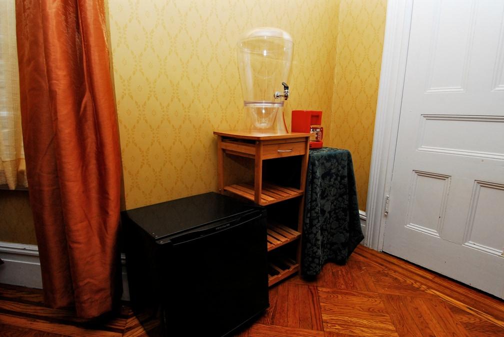 Mini-fridge, kitchen cart and coffee pot.