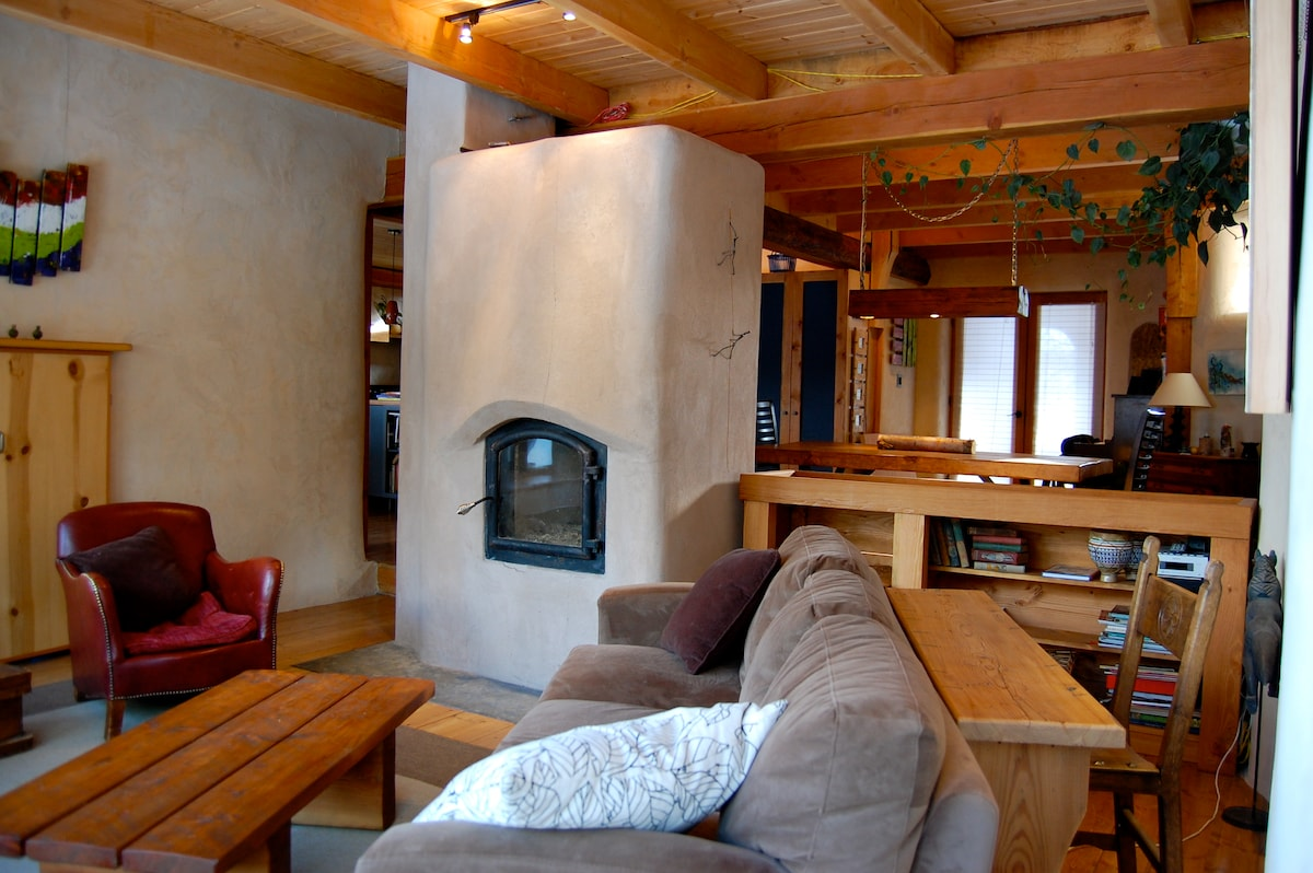 The LakeHouse - living room looking to dining room and kitchen with masonry wood stove.